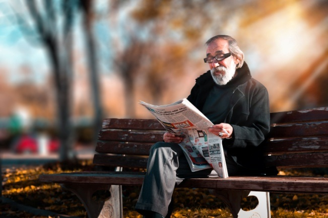 photo of an elderly man reading a newspaper with presbyopia glasses